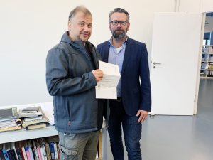 Claus Schröter, langjähriges Vorstandsmitglied des Xinnovations e. V., übergibt Armin Berger die Urkunde zur Kooption mit den Unterschriften aller Vorstandsmitglieder.